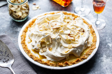 An amaretto cream pie topped with whipped cream and almonds