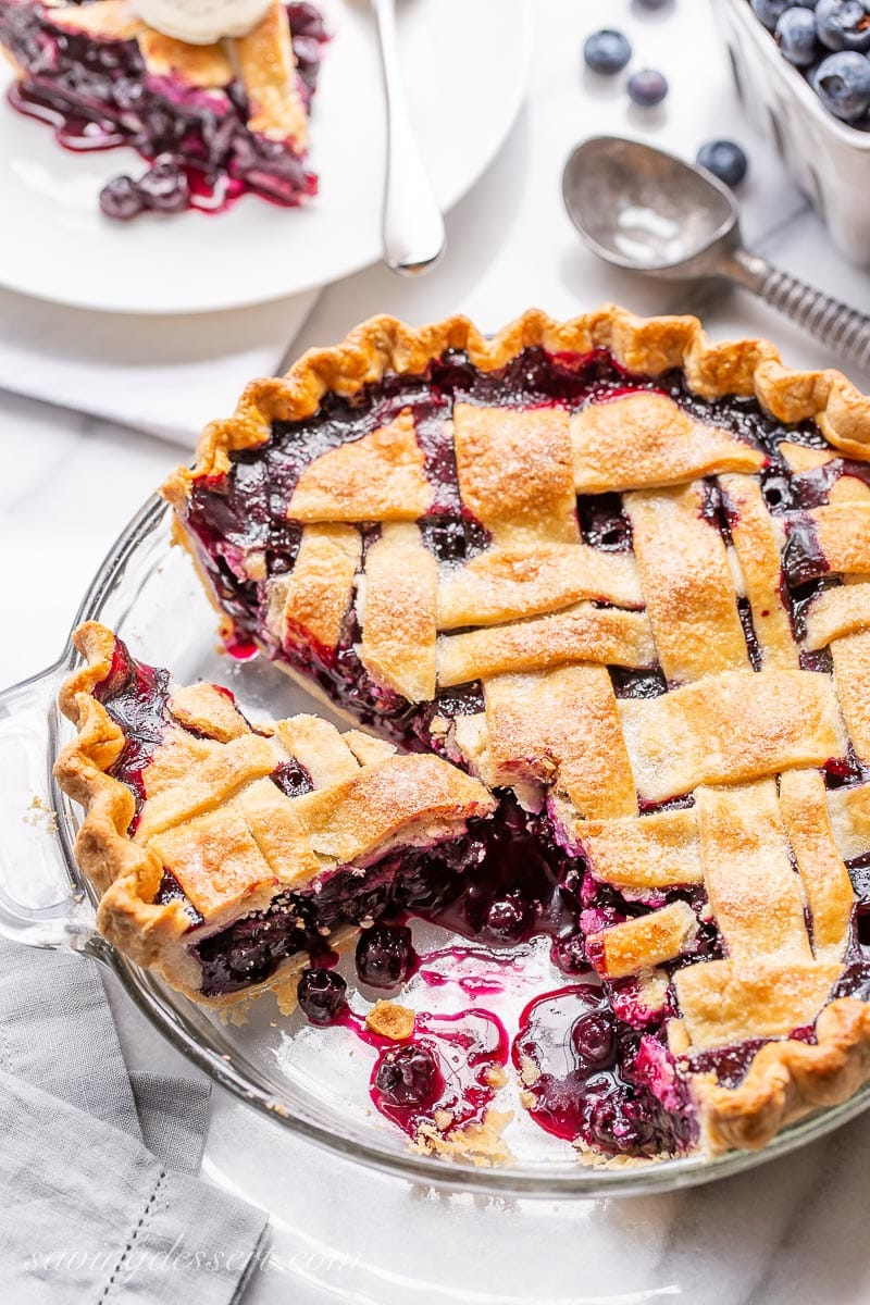 A sliced lattice topped blueberry pie with juicy blueberries in the pie plate