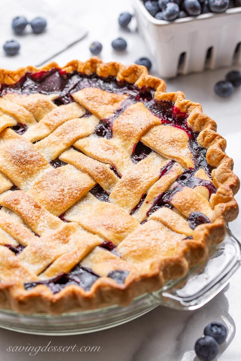 A side view of a lattice topped blueberry pie