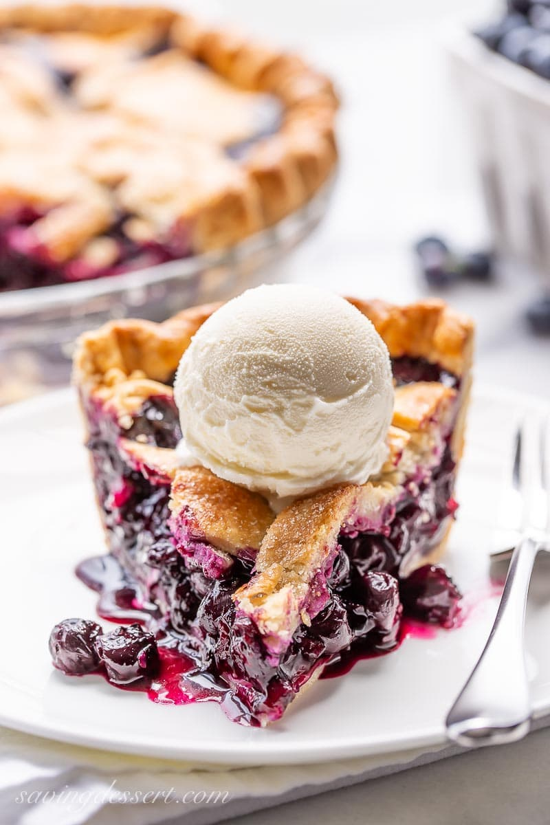 A slice of juicy blueberry pie topped with a scoop of vanilla ice cream