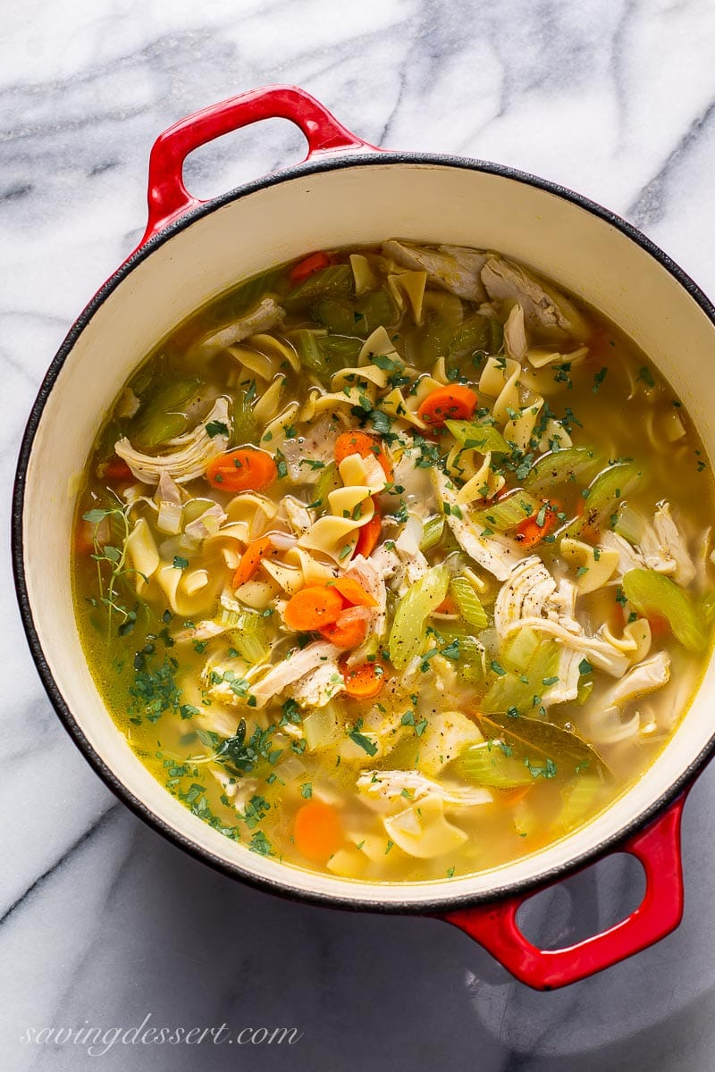 A Dutch oven filled with chicken noodle soup with carrots and celery