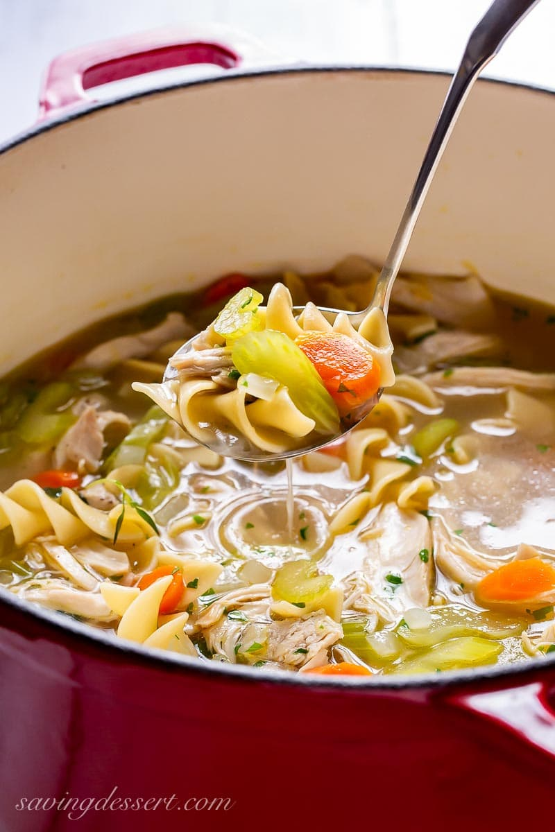 A ladle filled with noodles, carrots and chicken