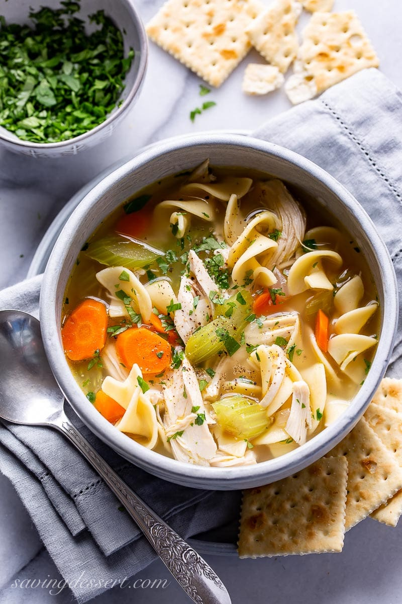 A bowl of chicken noodle soup served with crackers and garnished with parsley