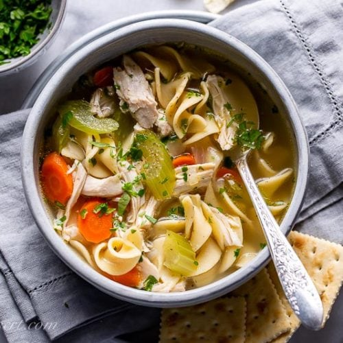 A bowl of chicken noodle soup served with crackers