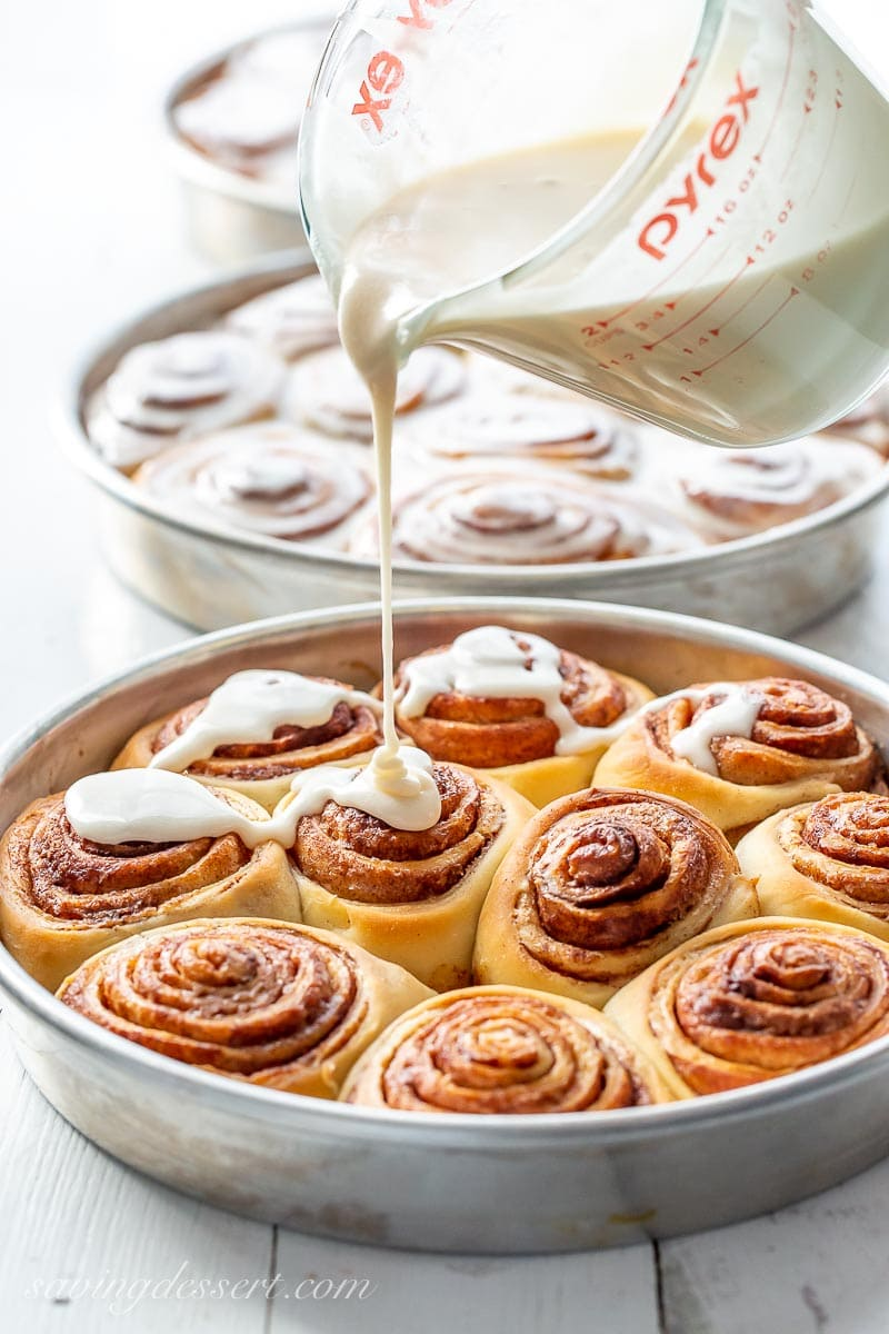 A pan of cinnamon rolls being drizzled with a maple frosting