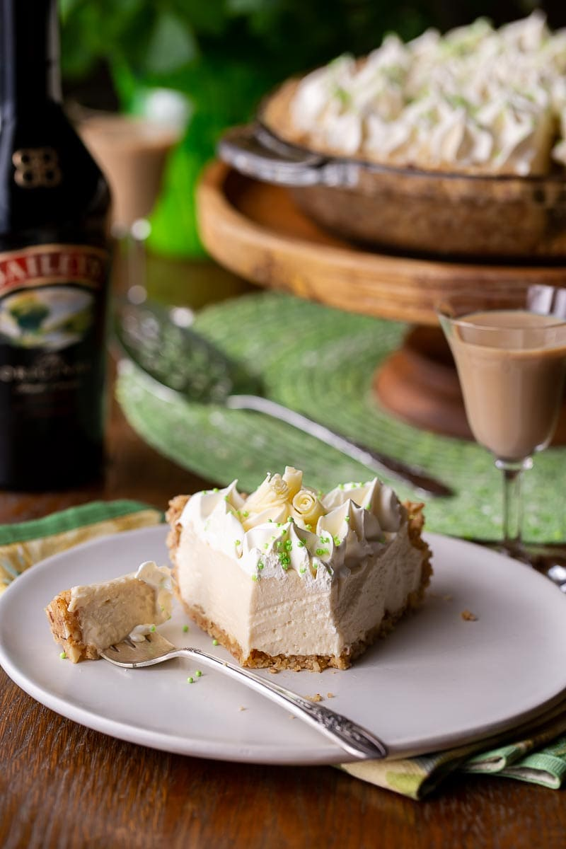 a slice of creamy pie on a plate served with Irish cream in a glass