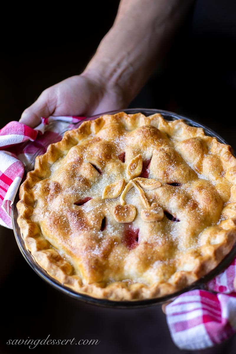 A hot cherry pie being held by a man