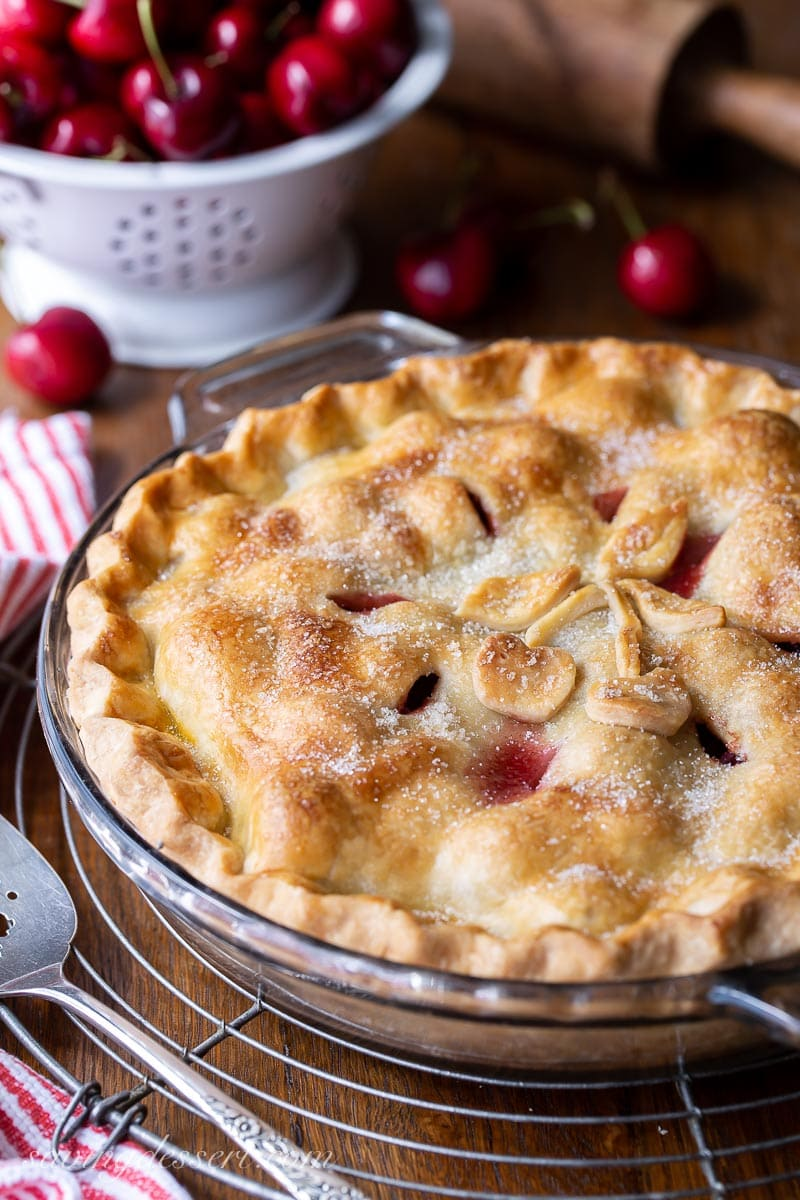 A homemade double crust pie on a cooling rack with fresh cherries in the background