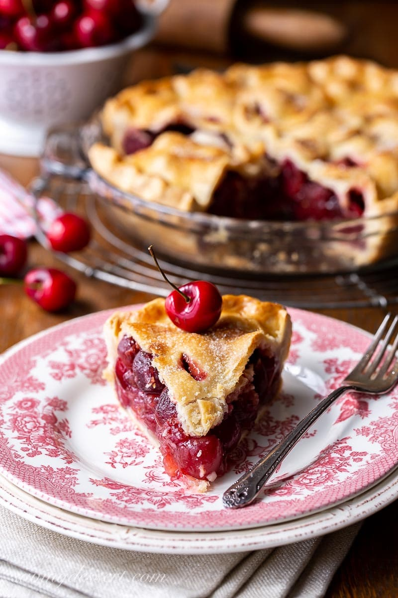 A slice of cherry pie with a fresh cherry on top