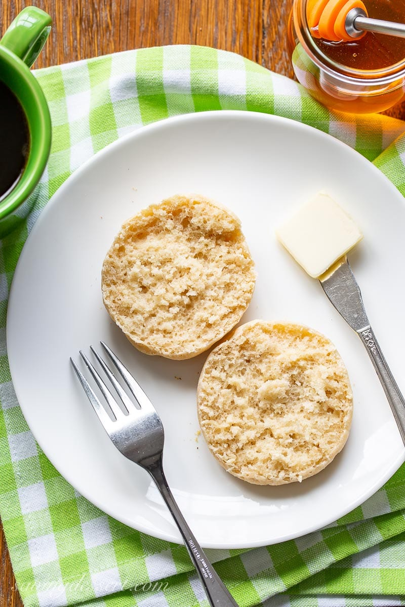 A split English muffin on a plate with butter