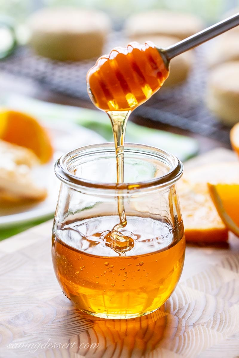 A jar of honey being drizzled