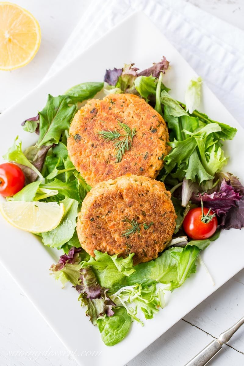 salmon patties served on a salad with fresh dill