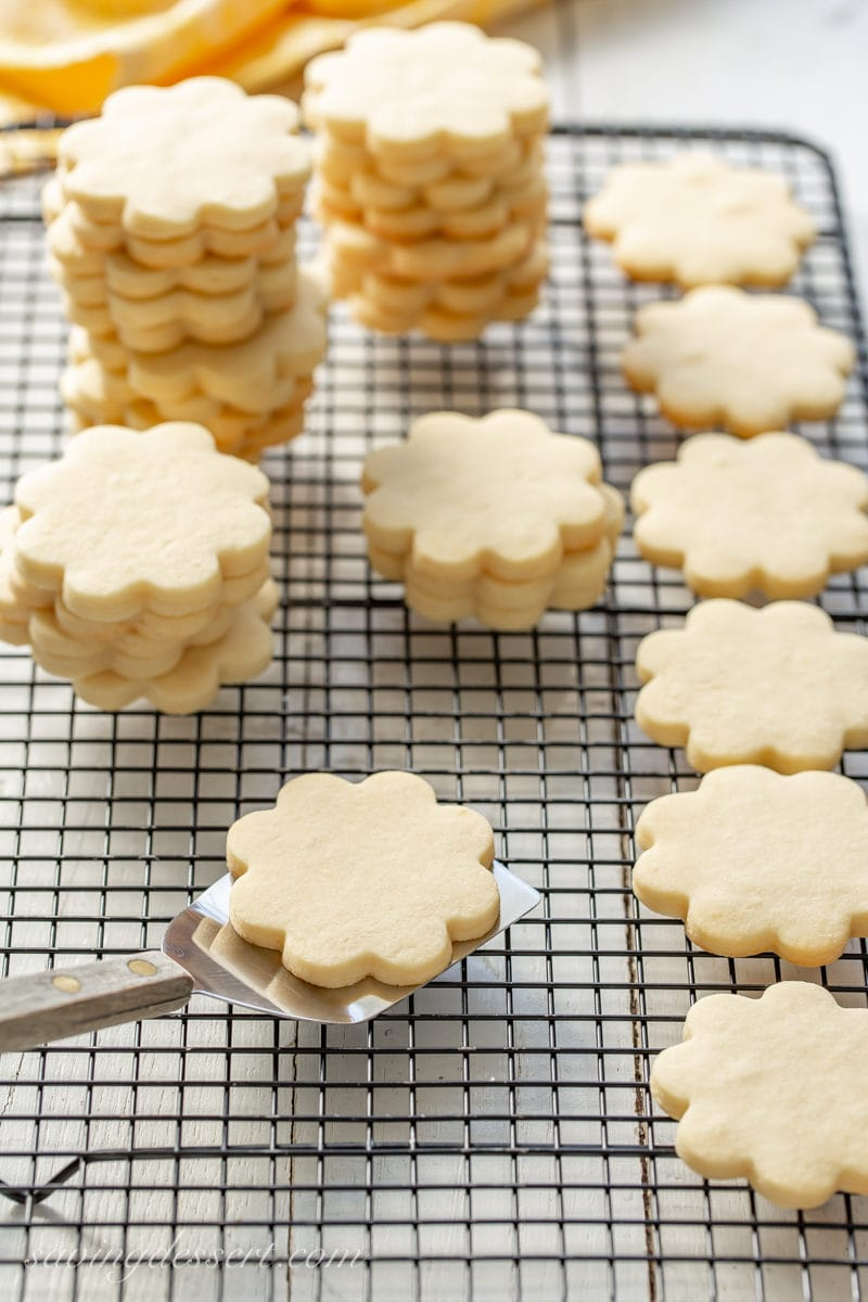 A cooling rack filled with flower shaped cut-out sugar cookies