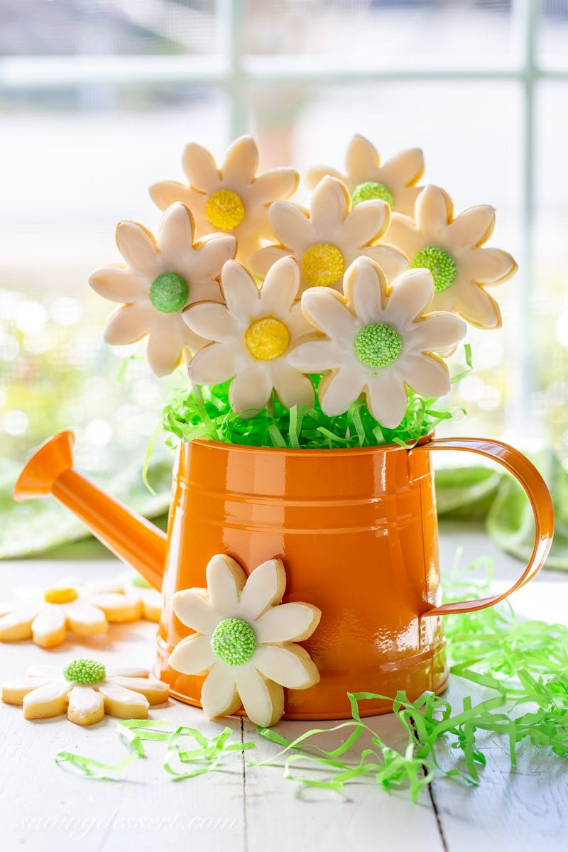A cookie bouquet filled with flower shaped cut-out sugar cookies, with green Easter basket grass in a watering can