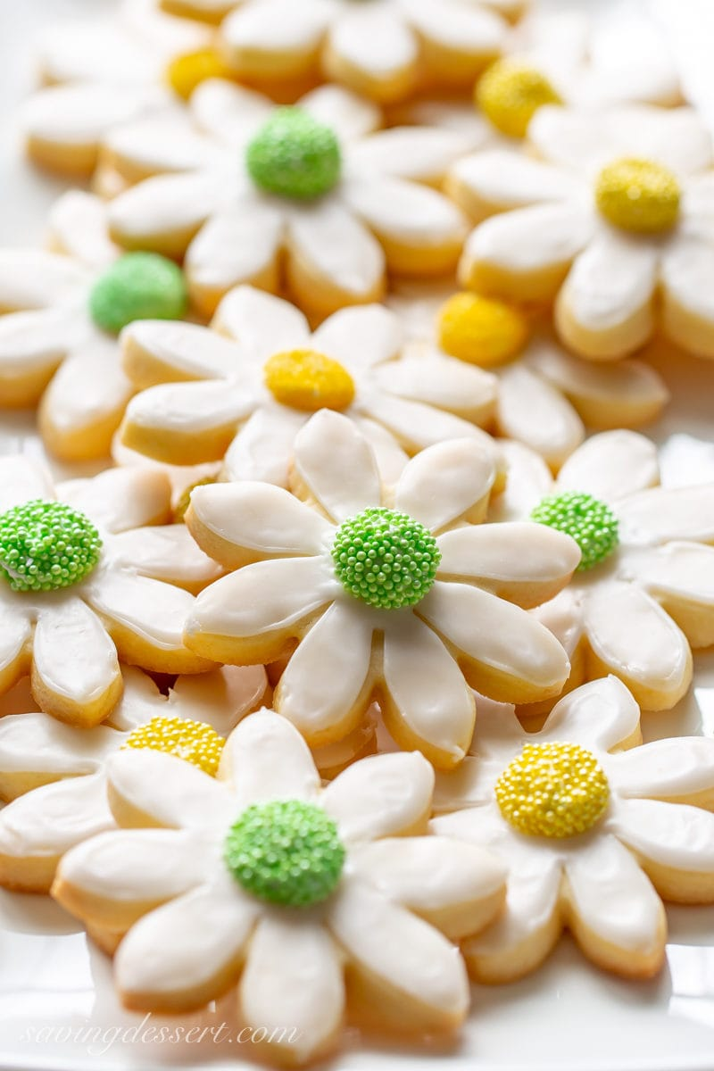 Thick flower shaped cut-out sugar cookies decorated with yellow and green sprinkles
