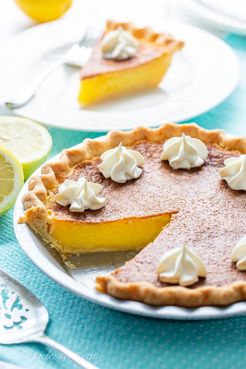 A sliced lemon pie with dollops of whipped cream on top