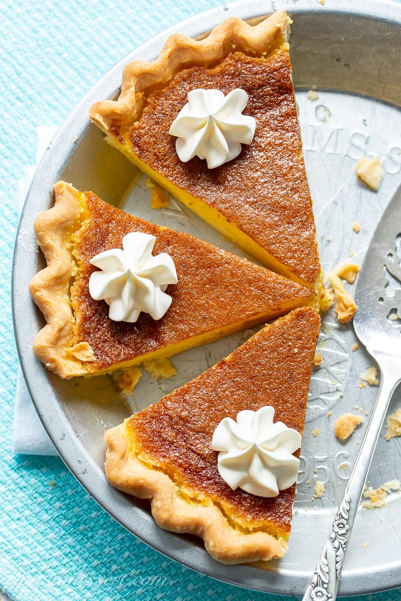 An overhead view of a sliced lemon pie with a golden brown top with swirls of whipped cream on each slice