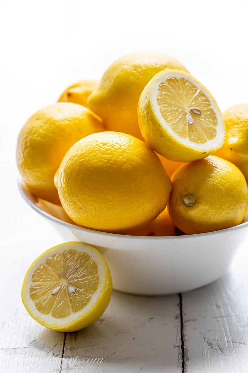 A bowl of fresh lemons with one sliced in half