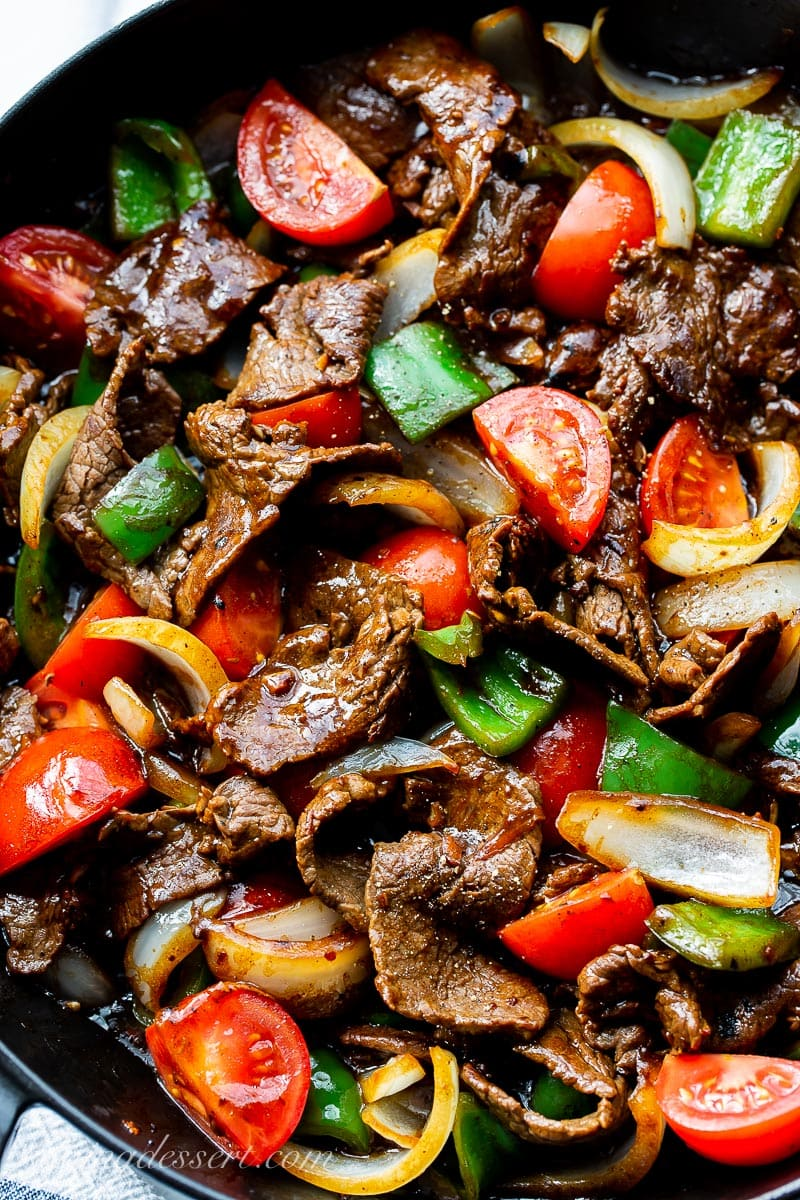 A closeup of a skillet with thin strips of steak with chunks of peppers, onions and tomatoes