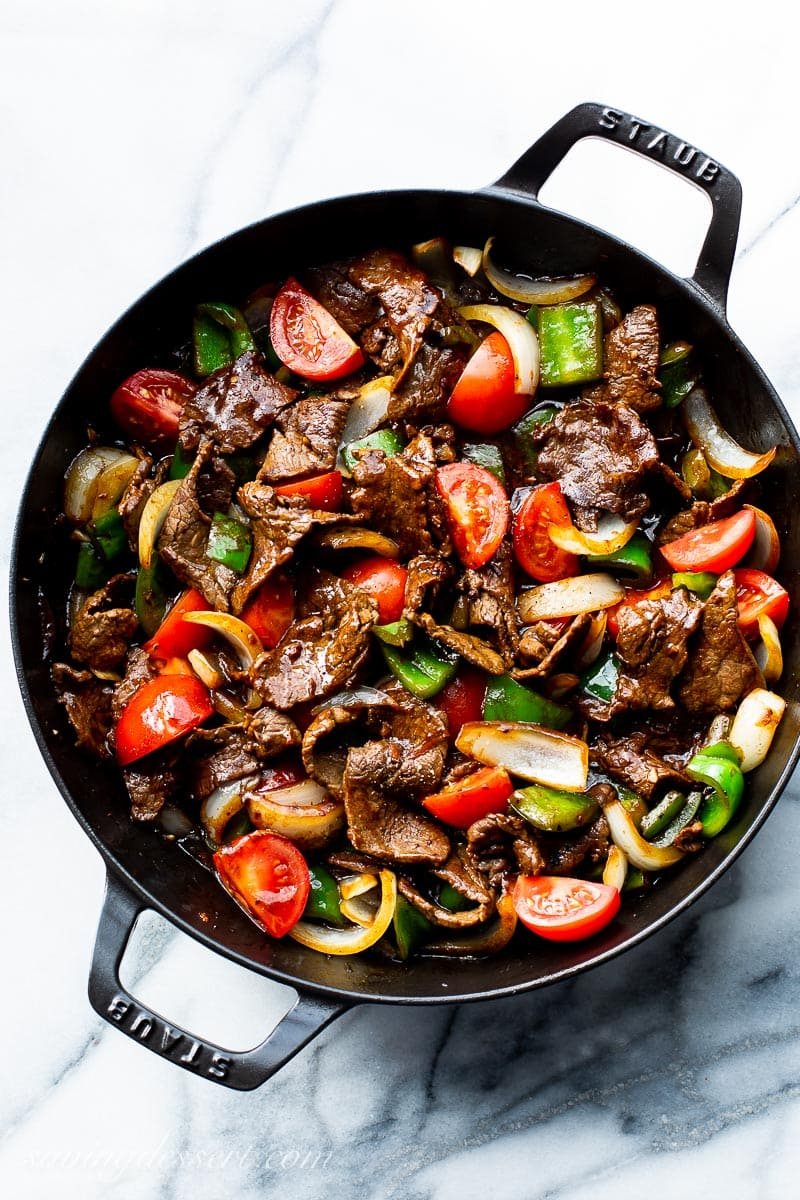 A skillet filled with thin strips of steak, peppers, onions and tomatoes