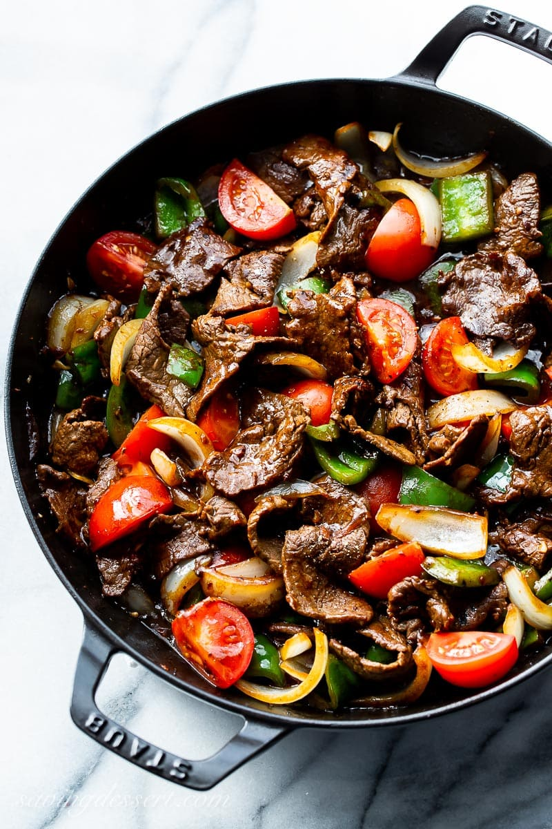 A skillet filled with steak, peppers, onions and tomatoes in a soy based sauce