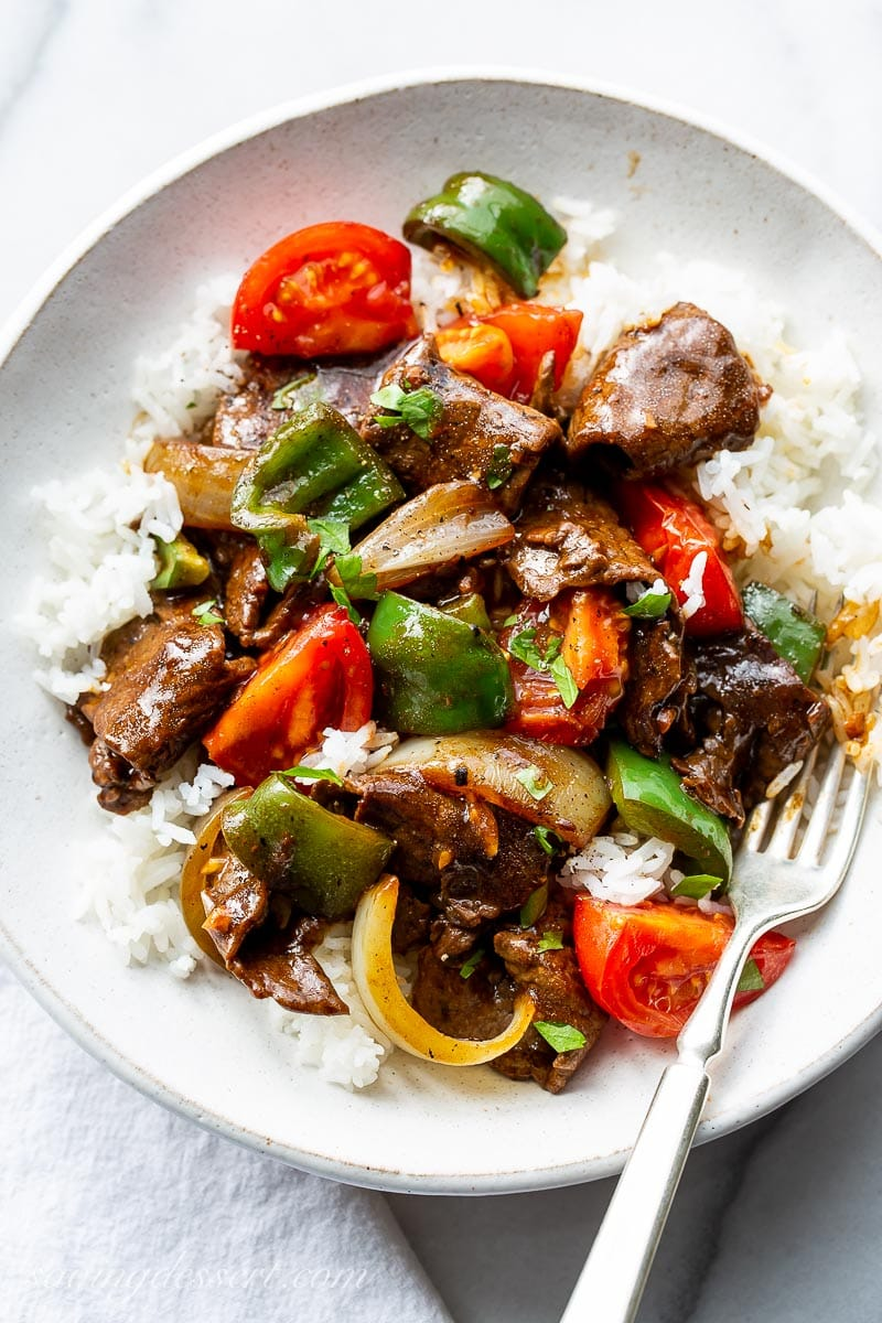 A bowl of rice topped with green pepper steak with tomatoes