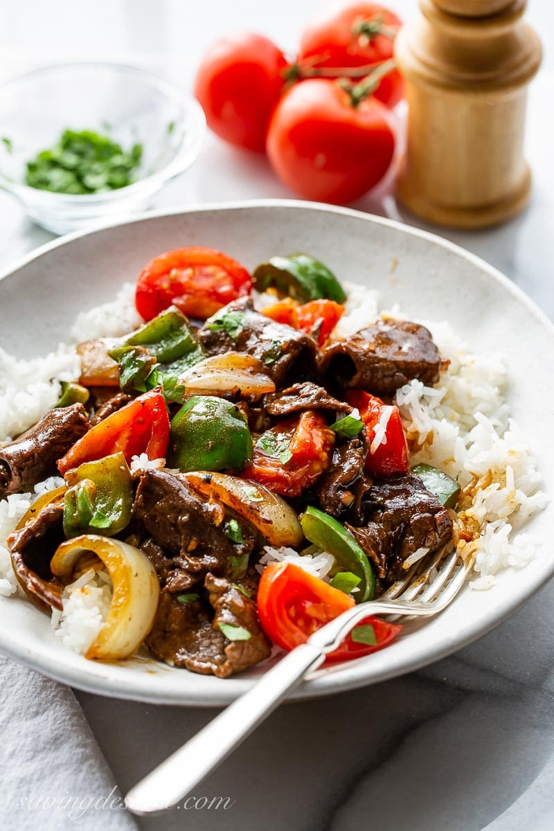 A big bowl with rice, pepper steak, onions, peppers and tomatoes garnished with parsley