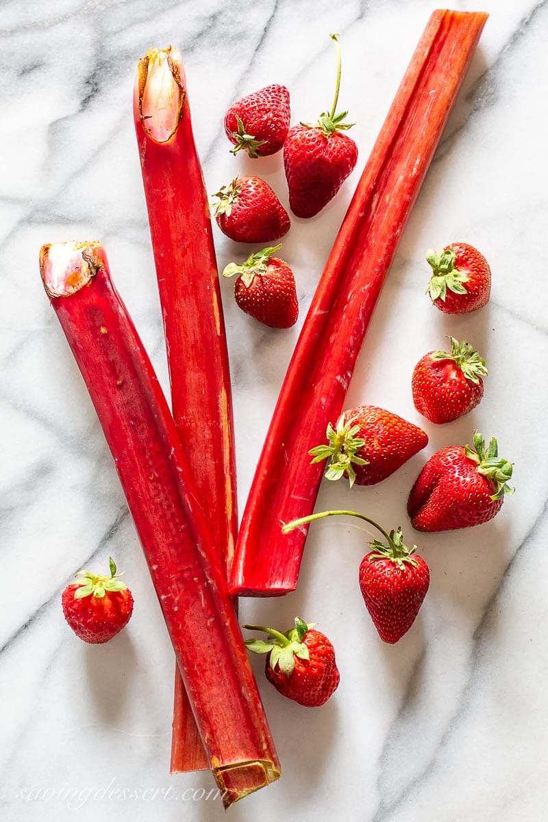 Rhubarb stalks with fresh strawberries on a marble slab