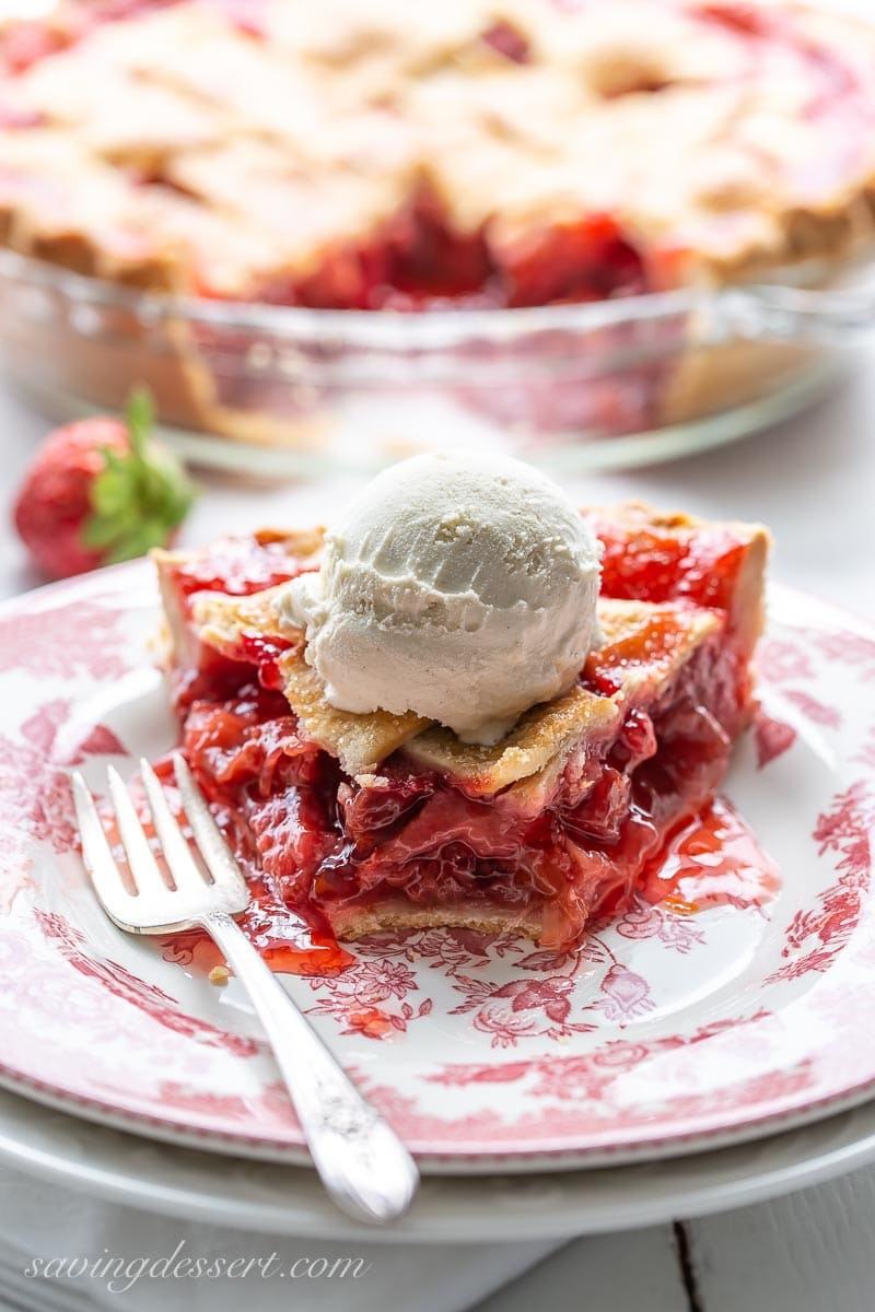A slice of strawberry rhubarb pie with ice cream on top