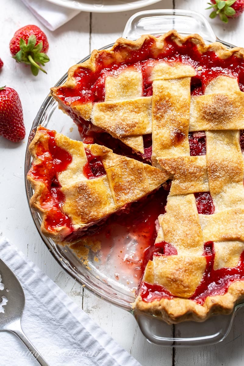 A sliced pie with a juicy red filling of strawberries and rhubarb topped with a lattice crust