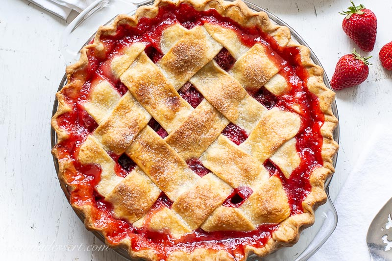 An overhead shot of a lattice crust pie made with strawberries and rhubarb