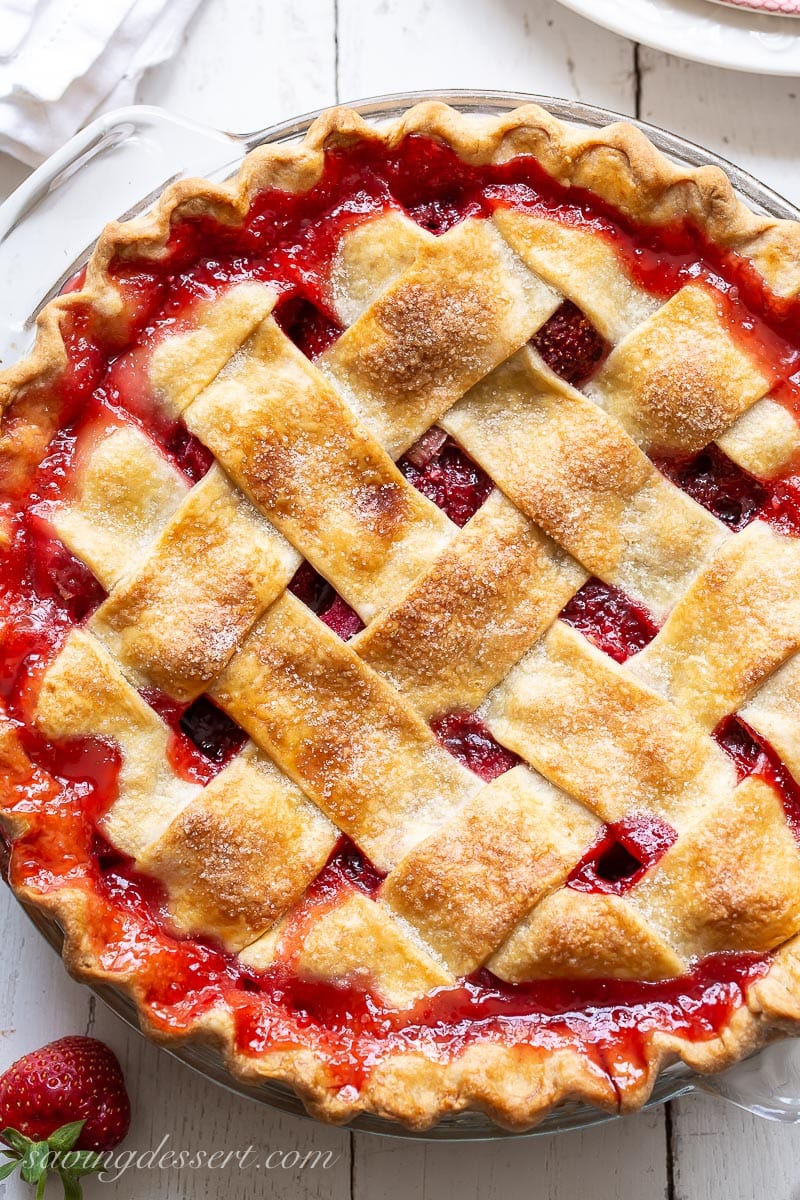 An closeup overhead view of a lattice topped strawberry rhubarb pie with red juices