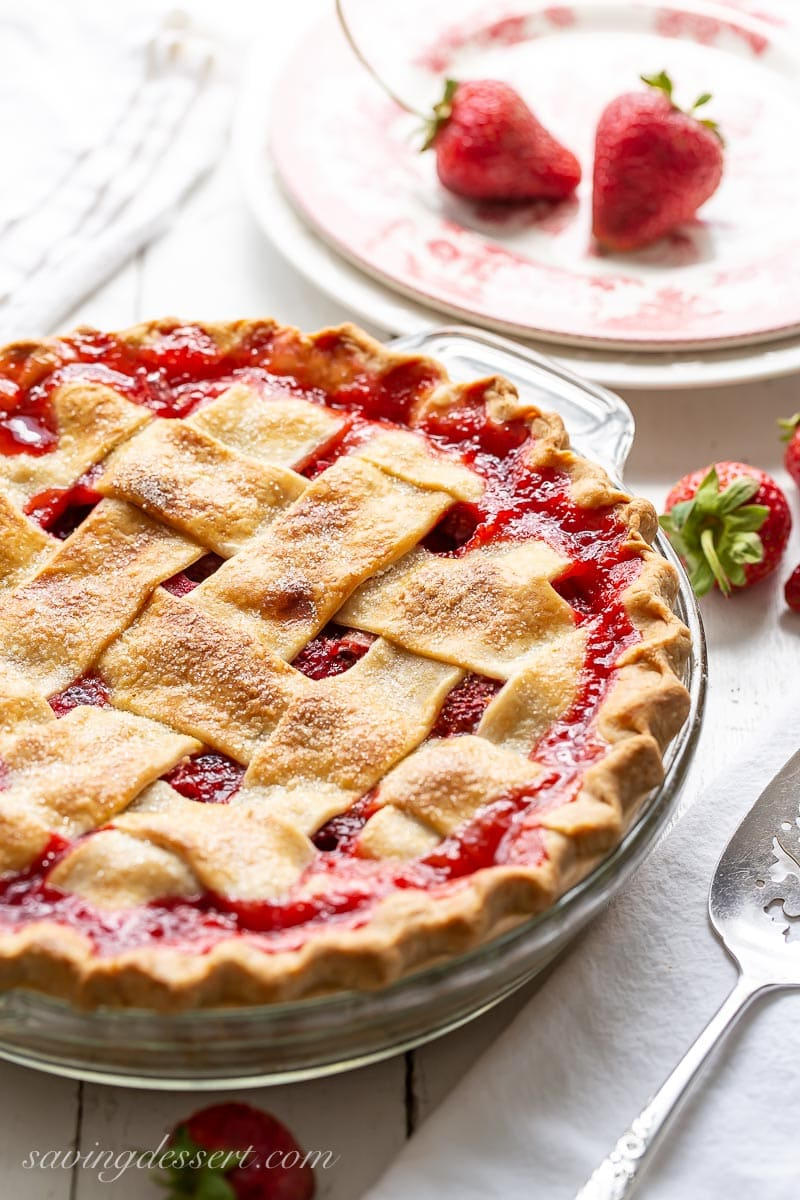 A strawberry rhubarb pie with a thick lattice crust with juices bubbling up between the crust