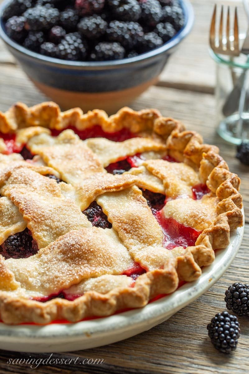 Blackberry pie with a lattice crust and a bowl of blackberries