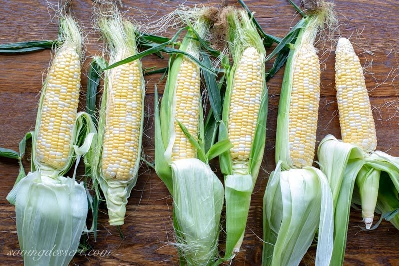 fresh summer ears of corn with husks and silk pulled down