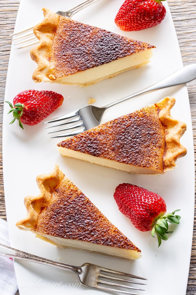 Slices of sugar cream pie on a platter served with strawberries