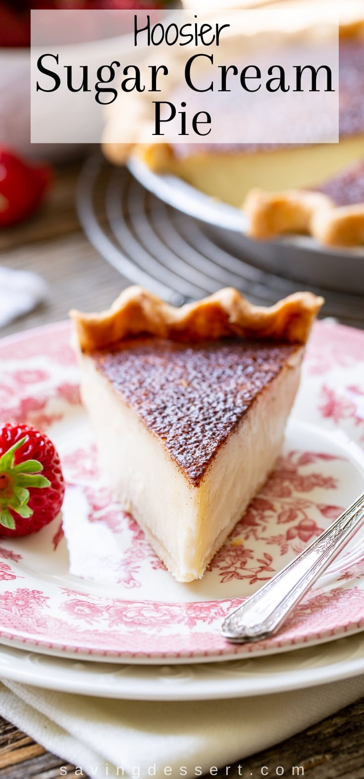 A slice of Hoosier Sugar Cream Pie on a plate served with strawberries