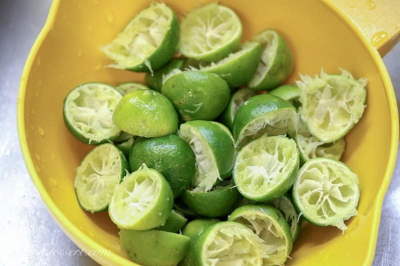 Key limes that have been juiced in a strainer