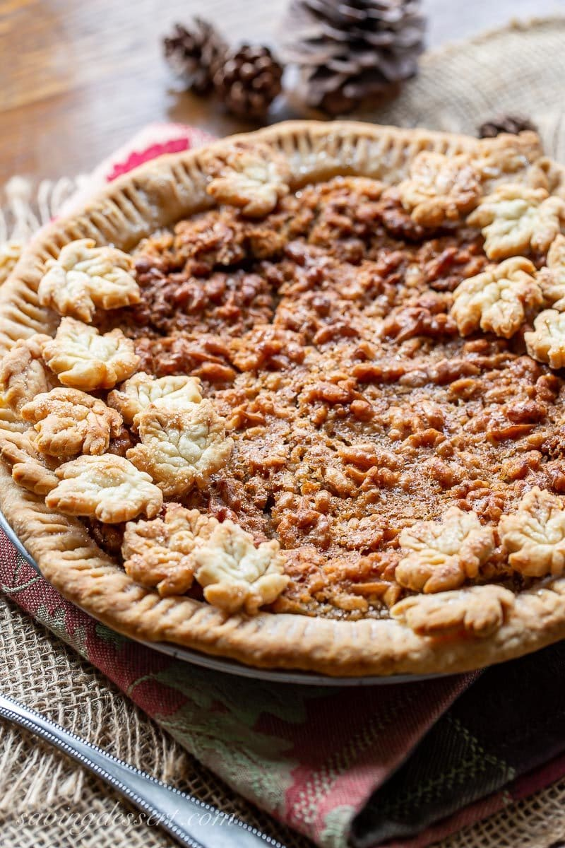 A side view of a maple walnut pie topped with crust cookies