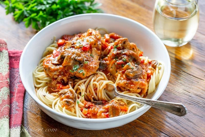 A bowl of spaghetti topped with Chicken Cacciatore with mushrooms, red peppers and parsley