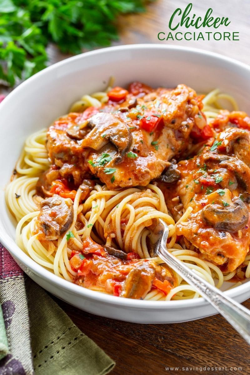 A big bowl of spaghetti topped with Chicken Cacciatore with mushrooms, red bell pepper and parsley