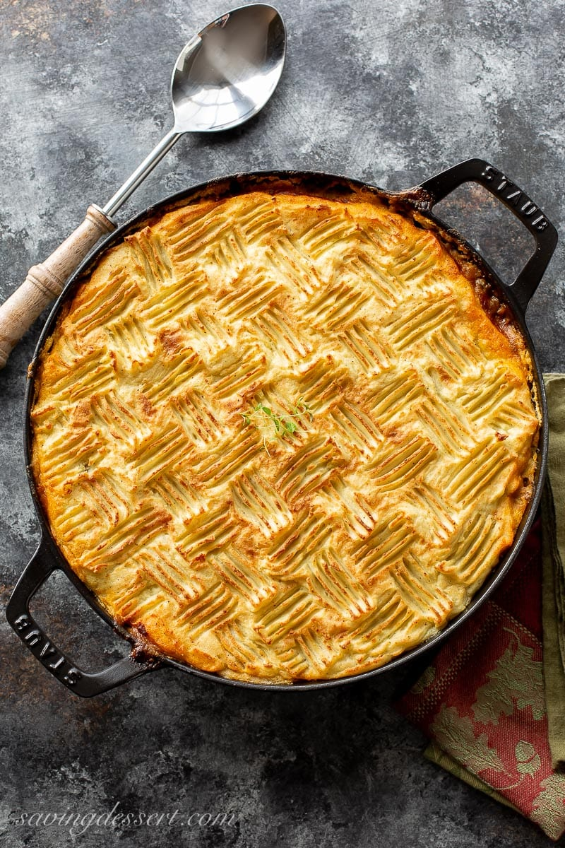 A skillet filled with cottage pie with mashed potatoes on top