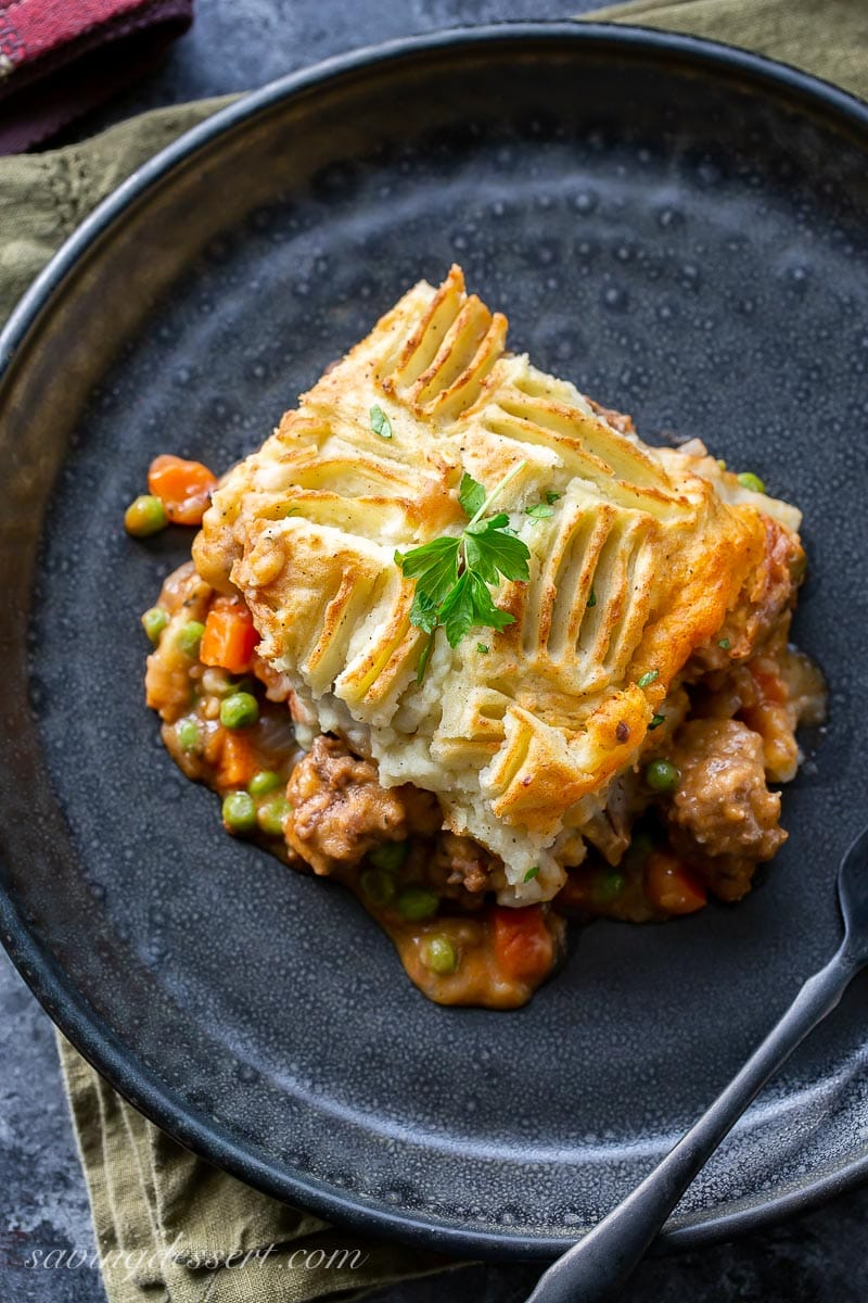 A plate with a helping of cottage pie topped with parsley