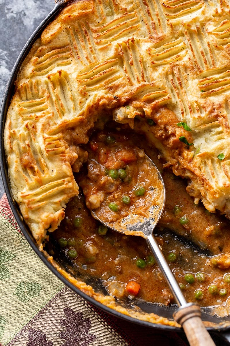 Cottage Pie topped with golden brown potatoes and a rich gravy with ground beef, carrots and peas