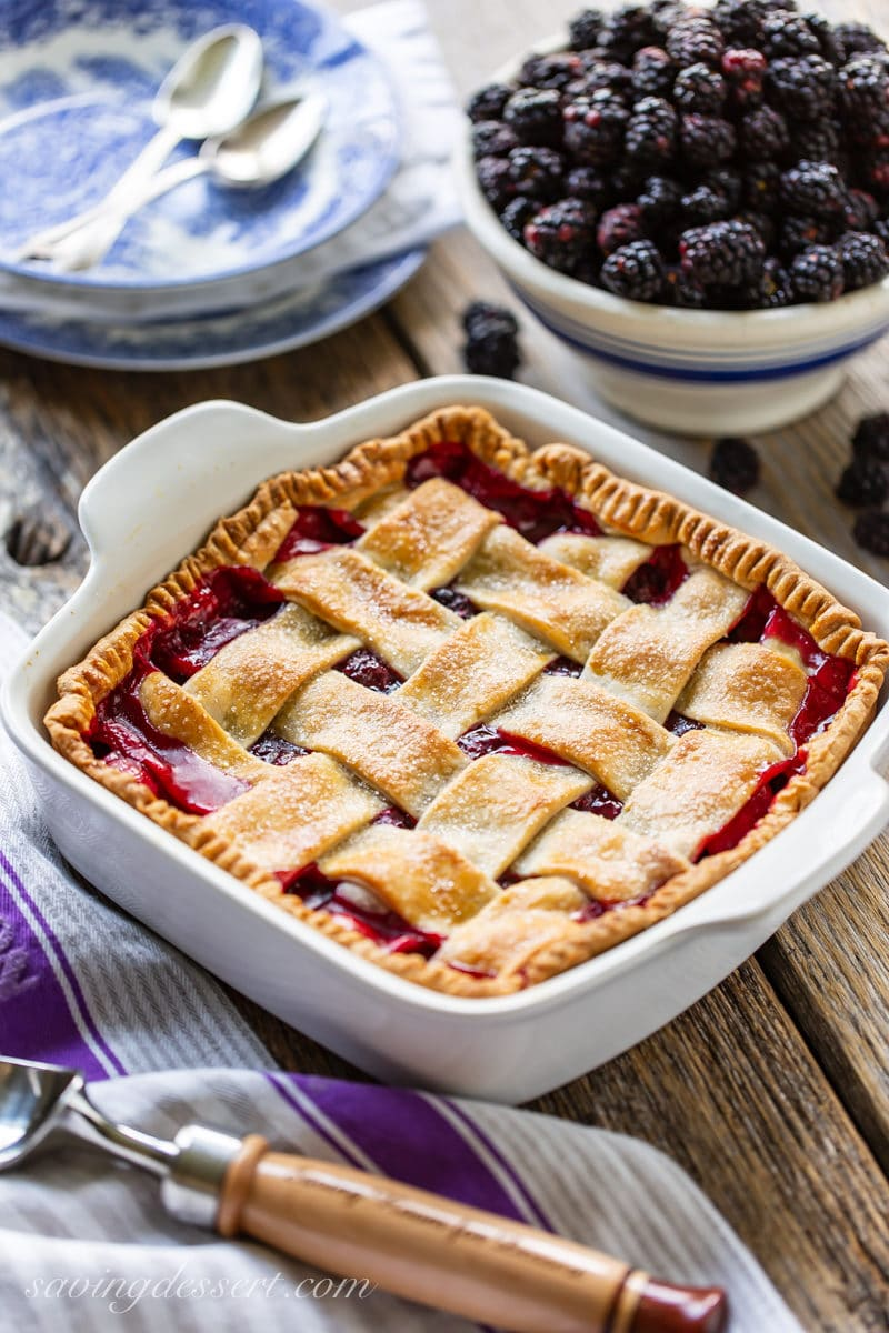 An old-fashioned blackberry cobbler with a lattice top and a bowl of fresh blackberries
