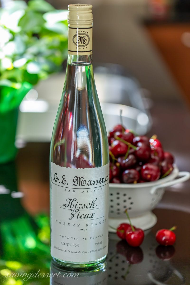 A bottle of cherry brandy and fresh cherries
