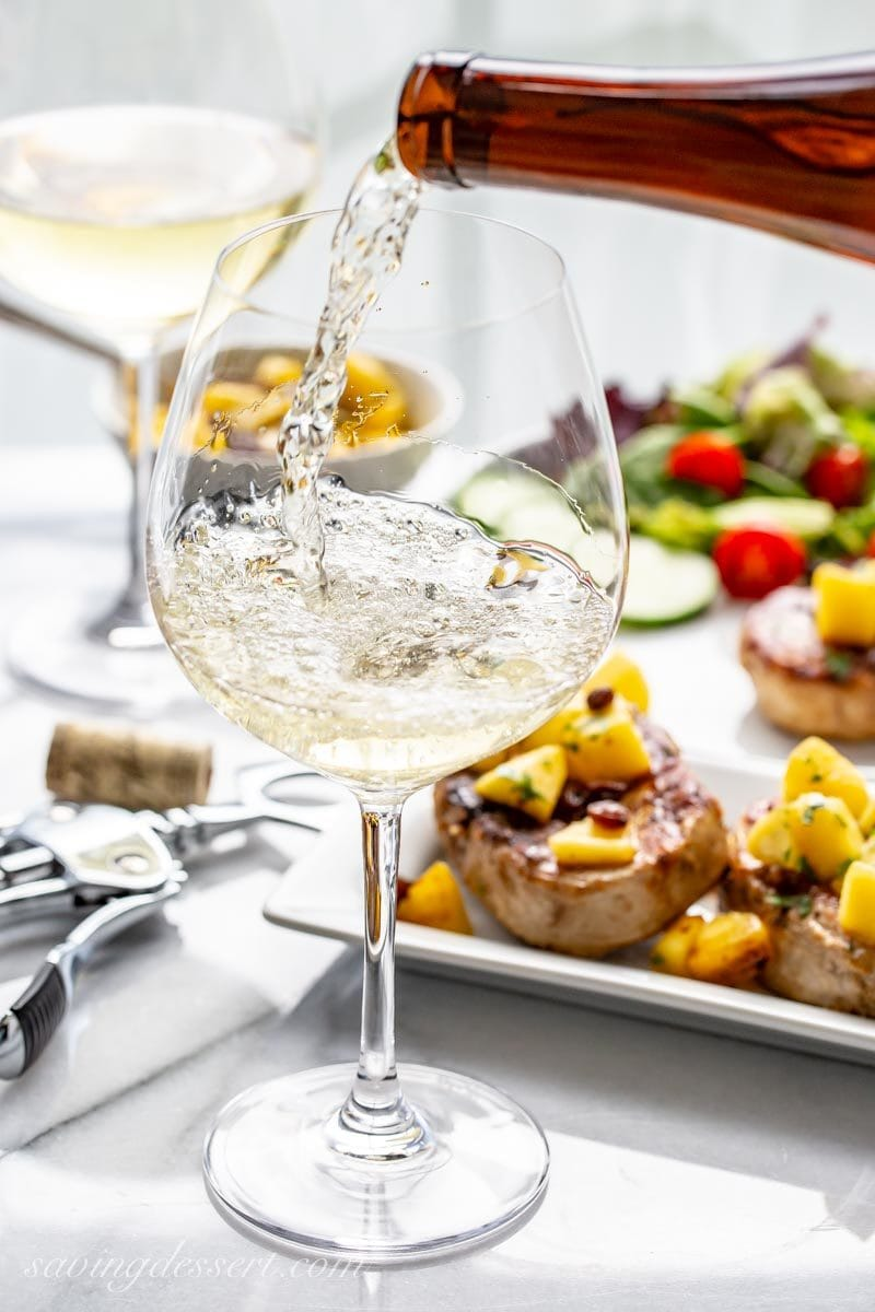 Glass of sweet Riesling wine with grilled pork chops with Peach Agrodolce