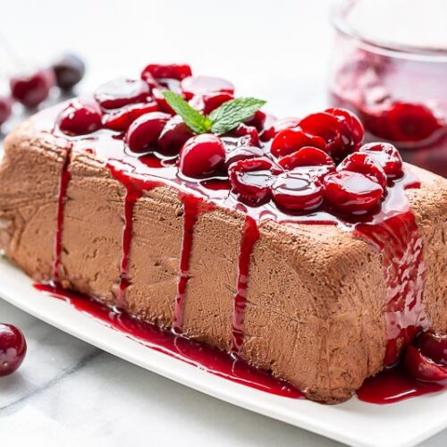 A side view of a molded Chocolate Marquise topped with fresh cherry sauce