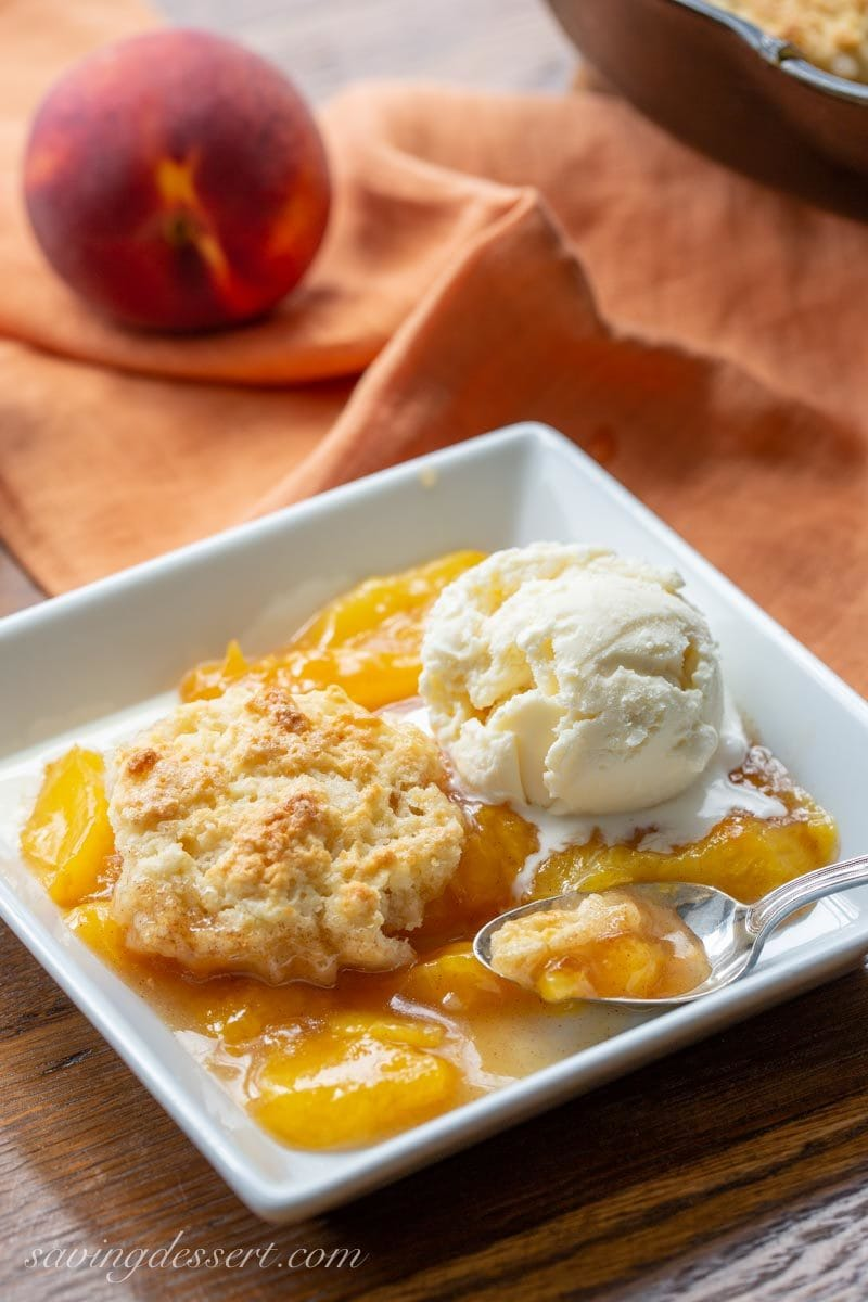 A bowl of old-fashioned peach cobbler topped with a scoop of ice cream