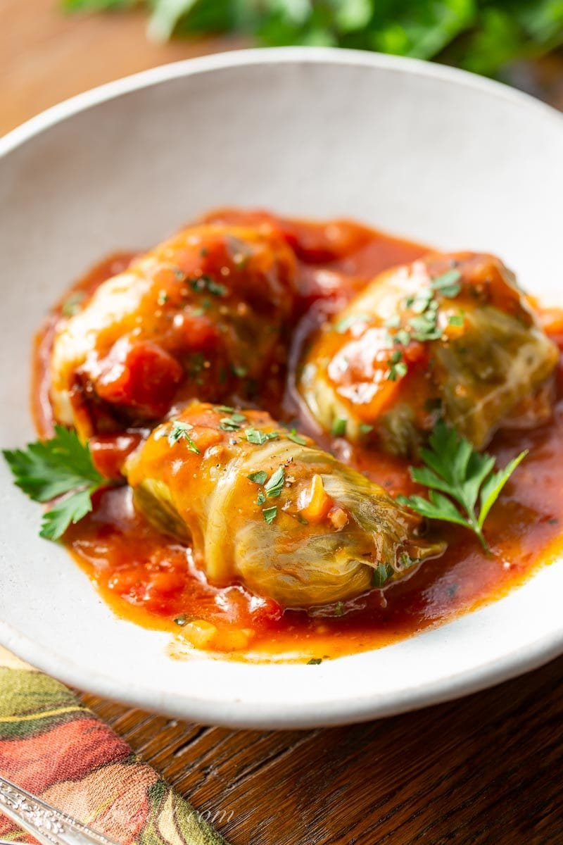 A bowl of cabbage rolls with a rich tomato sauce and parsley